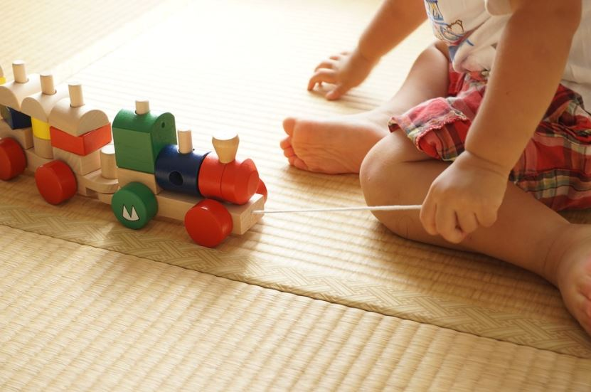 child playing with toy block train on play mat